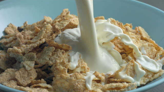 milk pours on cereal in slow motion. - milk stock videos & royalty-free footage