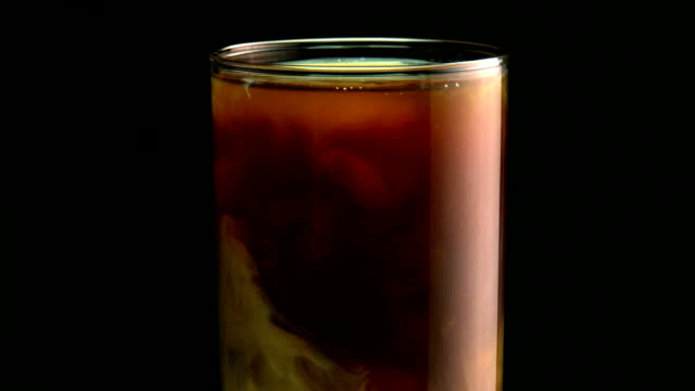 milk swirling in iced coffee or tea