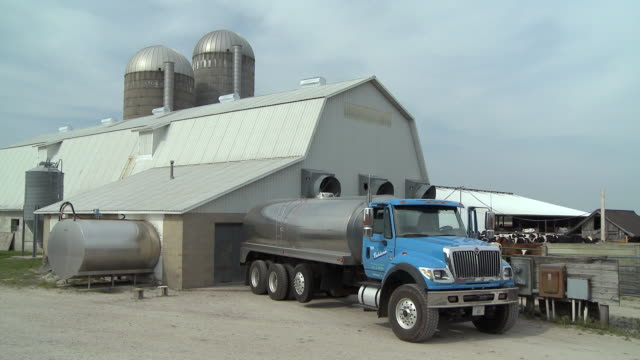 ms milk tanker driving away from dairy farm building, newark, illinois, usa - 乳製品工場点の映像素材/bロール