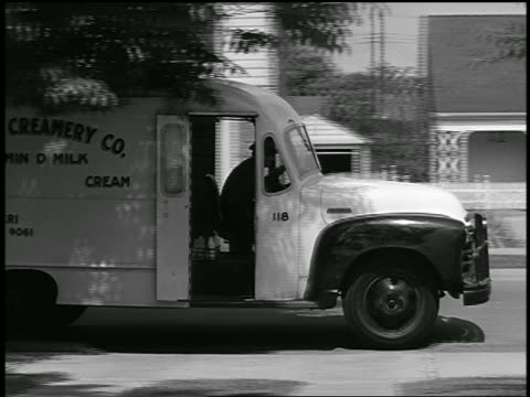 b/w 1948 pan milk truck parking + milkman getting out with milk bottles / industrial - 1948 stock videos & royalty-free footage
