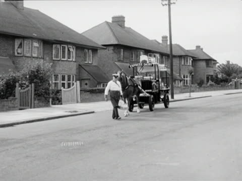 a milkman crosses a quiet suburban street to deliver milk his horse follows after him pulling the dairy cart and stops with its two front legs on the... - doppelhaus stock-videos und b-roll-filmmaterial