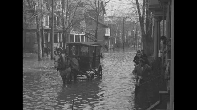 milkman steps through water from horsedrawn milk wagon in flooded street to deliver milk / coast guard dinghy on bed of truck in flooded street men... - milkman stock videos & royalty-free footage