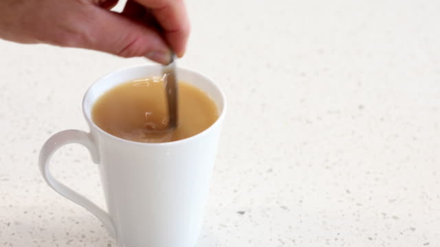 milky coffee or tea being stirred in a cup - loopable moving image stock videos & royalty-free footage
