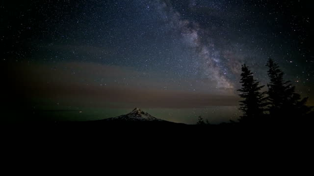 milky way and stars over snowy mountain mt. hood in summer from lost lake butte wide - mt hood stock videos & royalty-free footage