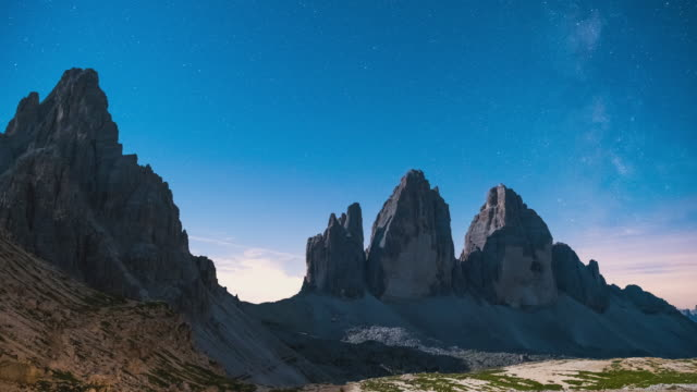 T/L Milky Way and sunrise Timelapse of Tre Cime di Lavaredo and Monte Paterno in the Dolomites, Italy -  wide shot