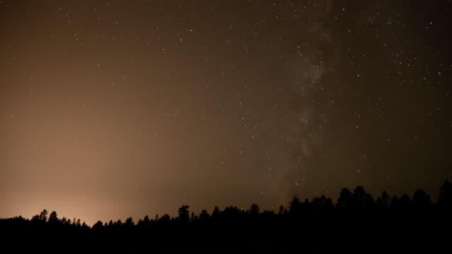 ws t/l milky way moving across sky over forest / flagstaff, arizona, united states - flagstaff arizona video stock e b–roll