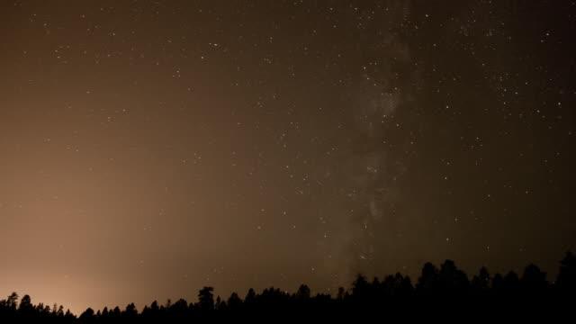ws t/l zi milky way moving across sky over forest / flagstaff, arizona, united states - flagstaff arizona video stock e b–roll
