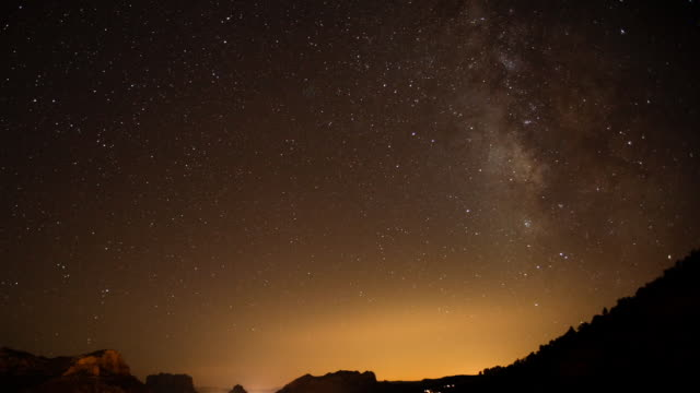 vídeos de stock, filmes e b-roll de ws t/l  milky way moving over city with traffic going through / sedona,  arizona, united states - sedona