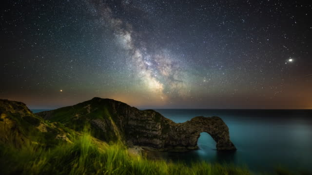 vídeos de stock e filmes b-roll de milky way over durdle door at night- time lapse - via láctea