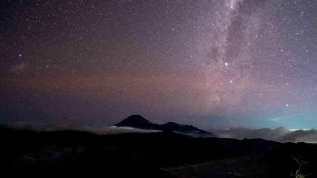 milky way over mount volcano with starry at night. batok, bromo, semeru, east java, indonesia - mount semeru stock videos & royalty-free footage