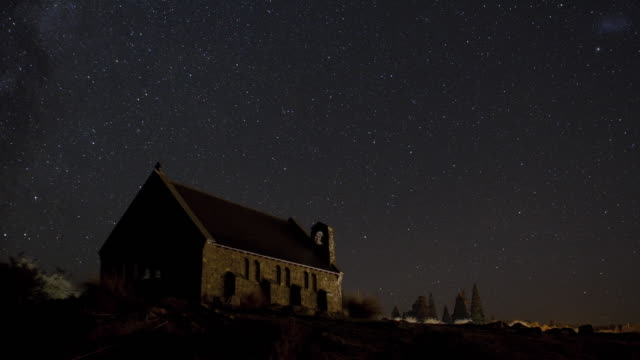 WS T/L Milky way rises behind an old church with glimpses of aurora australis / Lake Tekapo, New Zealand