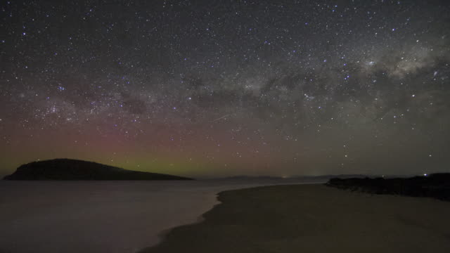 milky way setting over the ocean and a bright coloyrful display of the aurora australis or southern lights - aurora australis stock videos & royalty-free footage
