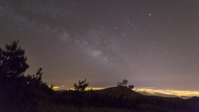 Milky Way time lapse over glowing clouds