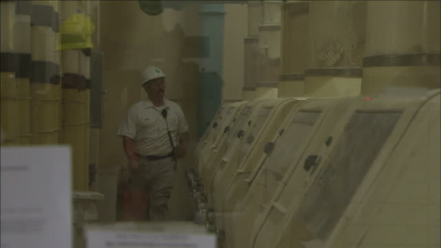a mill worker adjusts equipment in a wheat mill control room. - control room stock videos & royalty-free footage