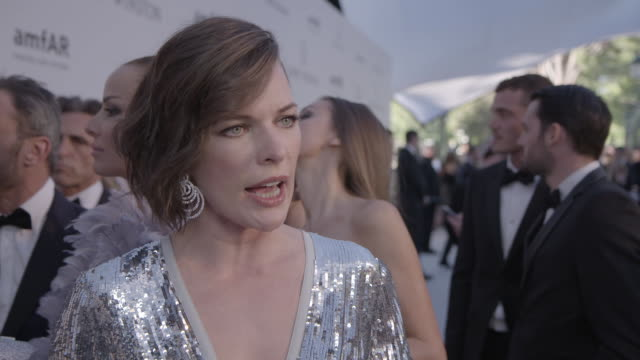 vídeos de stock, filmes e b-roll de interview milla jovovich on being at amfar on the achievements of aids research on the party at amfar's 23rd cinema against aids gala arrivals at... - milla jovovich