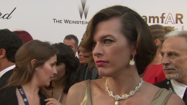 vídeos de stock, filmes e b-roll de milla jovovich on what amfar means to her and on elizabeth taylor at the amfar gala red carpet arrivals 64th cannes film festival at antibes - milla jovovich