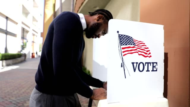 vídeos de stock e filmes b-roll de millenial black man voting in election - comício político