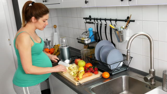 Millenial nine month pregnant woman at home, preparing fruit juice in kitchen