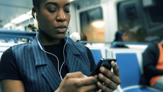 millenial texting while on the train - in ear headphones stock videos & royalty-free footage