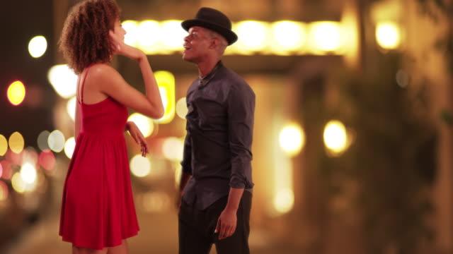 Millennial African American couple dance on a city street