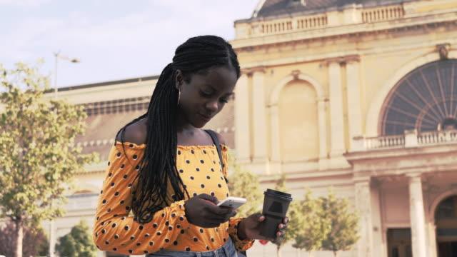 vídeos de stock e filmes b-roll de millennial african woman with braided hair using smart phone - handheld camera - braided hair