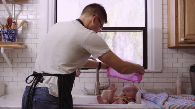 vídeos de stock e filmes b-roll de millennial aged father giving her daughter a sink bath - casa de banho