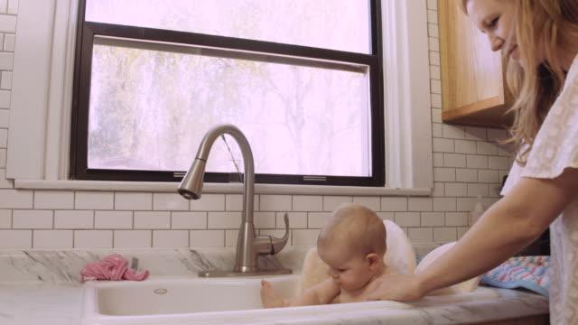 Millennial aged mother giving her daughter a sink bath