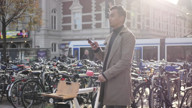 millennial asian man using mobile phone app - netherlands stock videos & royalty-free footage