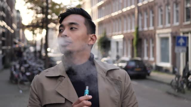 millennial asian man vaping outdoors - beautiful people stock videos & royalty-free footage