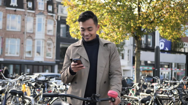 millennial asian man with bicycle using phone - netherlands stock videos & royalty-free footage