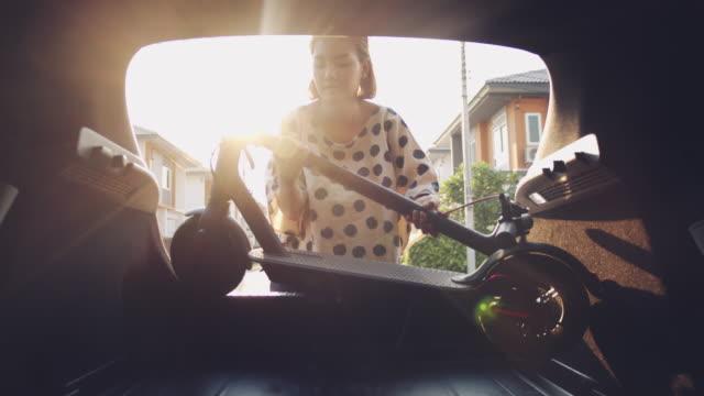 ミレニアル世代のアジアの女性は、休日に行く前にトランクに電動スクーターを入れています - 活動点の映像素材/bロール