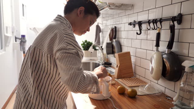 millennial asian woman making a orange juice in morning - electric juicer stock videos & royalty-free footage
