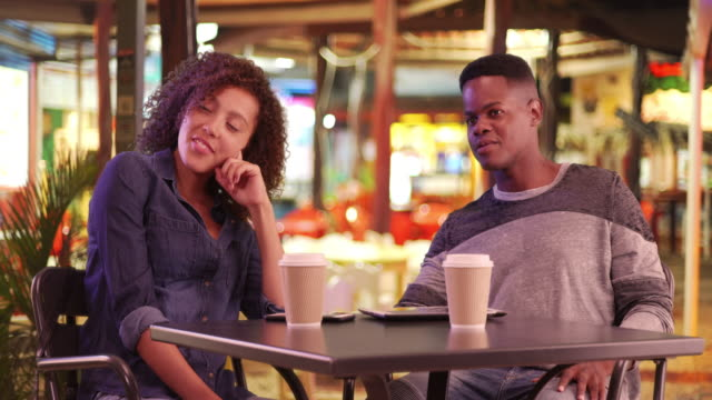 Millennial black couple have coffee at a cafe at night