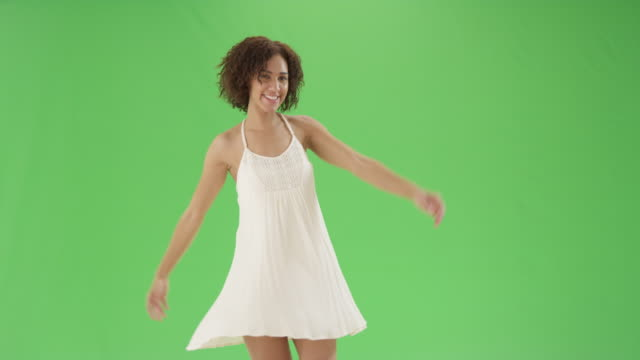 a millennial black girl dances around in a sundress on green screen - attraktive frau stock-videos und b-roll-filmmaterial