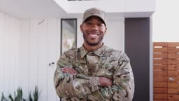 Millennial black male soldier steps towards camera, crosses arms and smiles to camera, close up