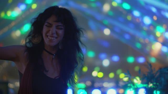 vídeos de stock e filmes b-roll de slo mo. a millennial bohemian woman rocks out under a music festival tent - cultura jovem