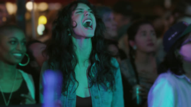 vídeos de stock e filmes b-roll de a millennial bohemian woman screams as rocks out in the front row of a popular music festival - rocking