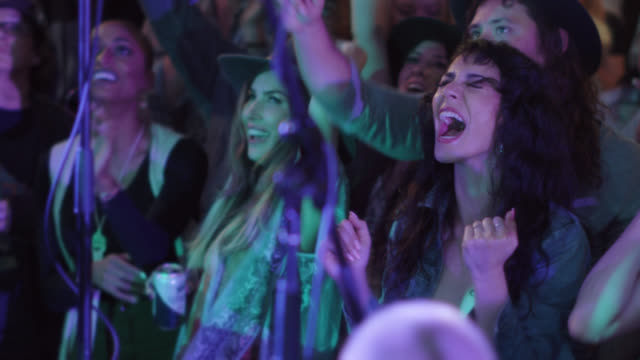 a millennial bohemian woman screams as she rocks out in the front row of a popular music festival - beatnik stock videos & royalty-free footage