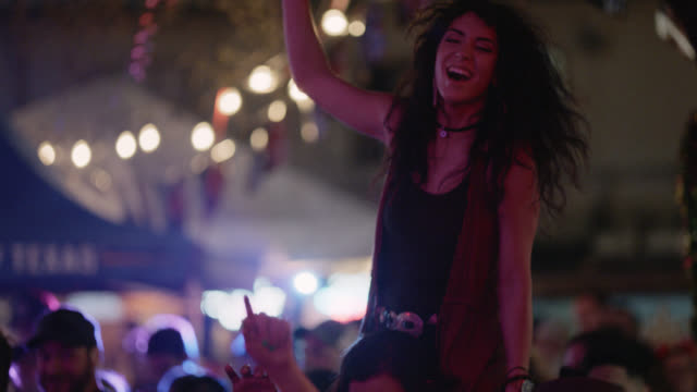 stockvideo's en b-roll-footage met slo mo. a millennial bohemian woman throws her hands in the air while riding on the shoulders of her significant other at a popular music festival - milleniumgeneratie