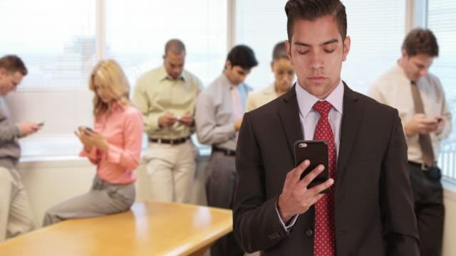 vídeos y material grabado en eventos de stock de millennial business man texting in office surrounded by coworkers using their own smartphones - compromiso de los empleados