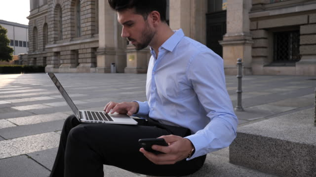 millennial businessman synchronizing laptop and mobile phone - slow motion 4k video - full suit stock videos and b-roll footage
