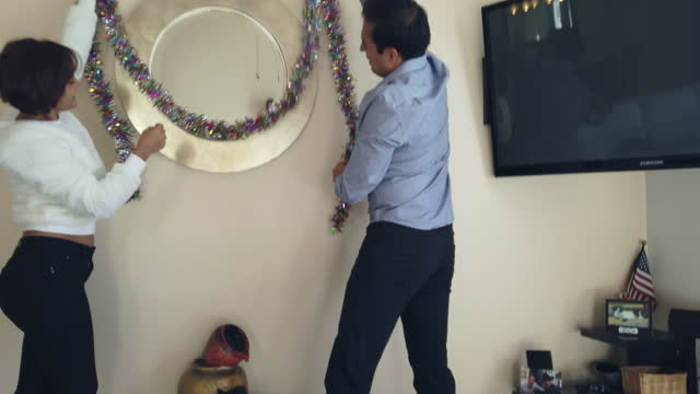 一致する静止画とクリスマス4kビデオシリーズの準備自宅でミレニアルコロンビアの民族カップル - ティンセル点の映像素材/bロール