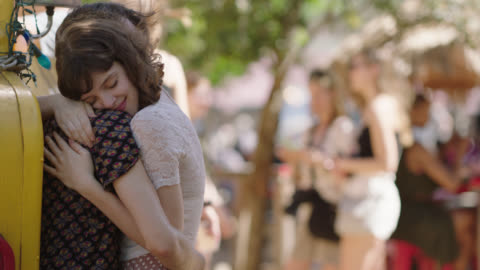 millennial couple embrace and kiss at an outdoor festival. - young couple video stock e b–roll