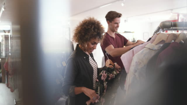 millennial couple in a vintage clothing store - armeria negozio video stock e b–roll
