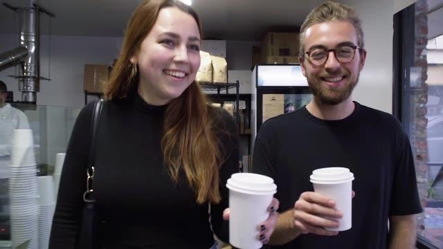 Millennial par lämnar ett kvarter Coffee Shop