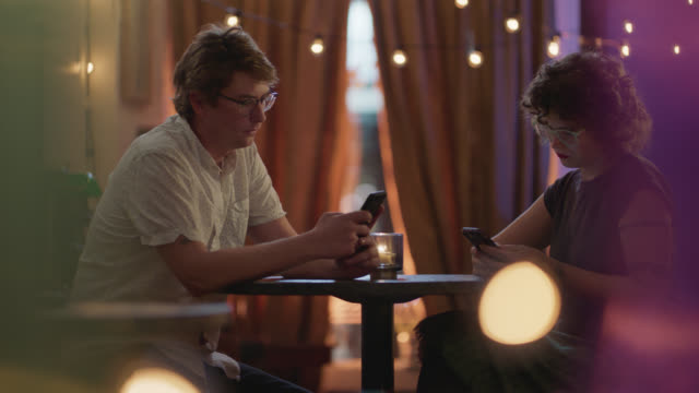 a millennial couple sits together at a table looking at their phones ignoring each other - disrespect stock videos & royalty-free footage