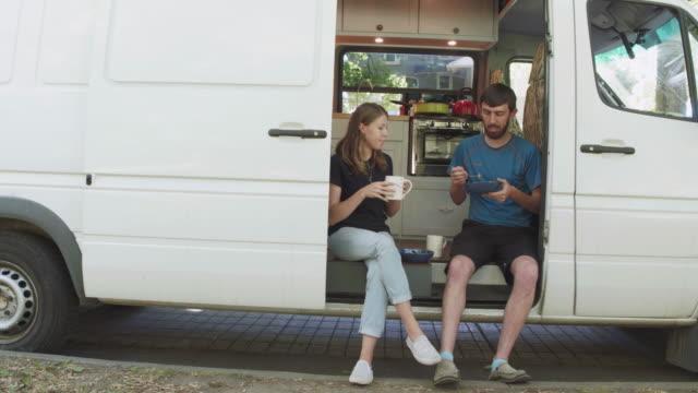 tausendjährige paar sitzt in der tür ihres hauses van - wohngebäude innenansicht stock-videos und b-roll-filmmaterial