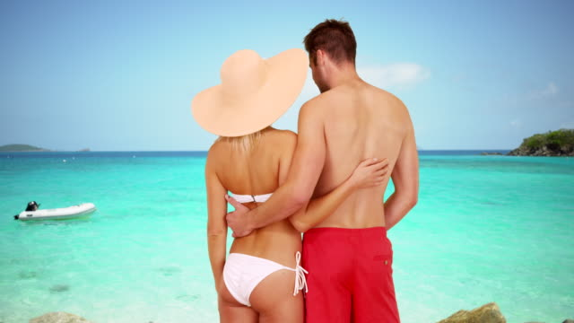 Millennial couple standing together looking at the clear water