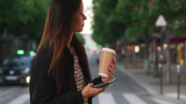 Millennial female with her coffee texting with cell phone while on city street