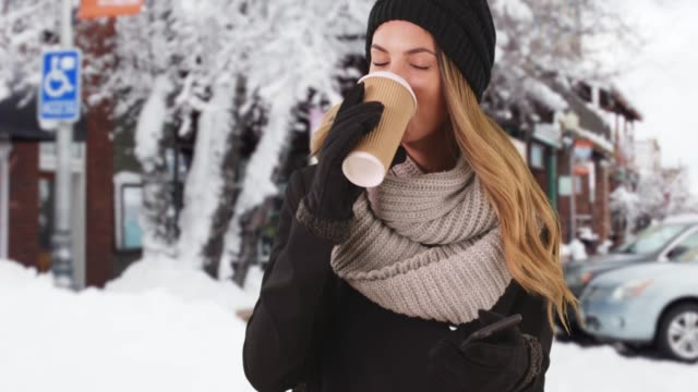 millennial girl drinking coffee outside in the snow rolling her eyes at her phone - rolling eyes stock videos & royalty-free footage